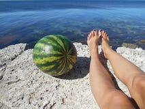 Weibliche Beine und Wassermelone auf einem Meer Stockfotos