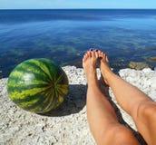 Weibliche Beine und Wassermelone auf einem Meer Lizenzfreie Stockfotografie