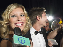 Weibliche Berühmtheit, die in Mikrofon spricht Stockfoto