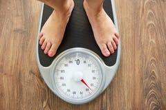 Weibliche bloße Füße auf Gewichtsskala Lizenzfreies Stockfoto