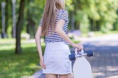 Weibliche blonde Jugendlich-Rückseiten-Ansicht Mit Longboard draußen aufwerfen Lizenzfreies Stockfoto