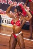 Weibliche Bodybuilder in den doppelten Bizepsen werfen und roter Bikini auf Lizenzfreies Stockfoto