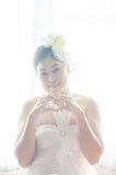 Weibliche Braut des Porträts mit den Händen, die ein Herzsymbol auf Fensterweißhintergrund formen Stockfotografie