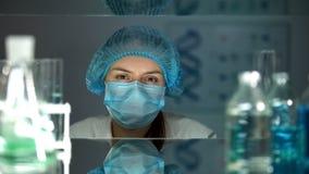 Weibliche Chemikalie in der sch?tzenden Uniform, welche die Kamera, arbeitend im Labor betrachtet stockfoto