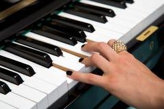 Weibliche Damenfinger auf den Klavierschlüsseln Stockbild