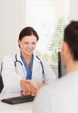 Weibliche Doktorhand, die mit einem Patienten rüttelt Stockfotografie