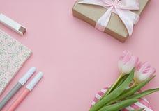 Weibliche Ebene legen Rahmen mit Blumen und Geschenk auf den rosa Hintergrund Kopieren Sie Platz Stockfotografie