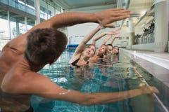 Weibliche Eignungsklasse, die Aquaaerobic mit männlichem Lehrer tut Lizenzfreie Stockfotografie