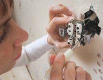 Weibliche Elektrikerreparatur der Ausgang auf der Wand stockbilder