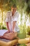 Weibliche empfangende Rückenmassage von einem Massagefachmann am bea lizenzfreie stockfotos
