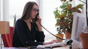 Weibliche Empfangsdame, die an Computer arbeitet und am Telefon in Call-Center spricht stock footage