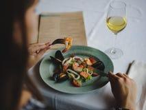 Weibliche Essenmeeresfrüchte der Nahaufnahme Eine Platte von Garnelen und von Glas Wein auf einem Tabellenhintergrund Restaurantk Stockfotografie