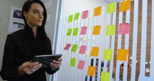 Weibliche Exekutive, die klebrige Anmerkung bei der Anwendung der digitalen Tablette 4k entfernt stock video