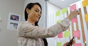 Weibliche Exekutive, die klebrige Anmerkung bei der Anwendung der digitalen Tablette 4k entfernt stock video footage