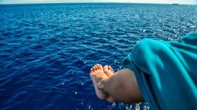 Weibliche Füße über dem Ozean Lizenzfreie Stockfotografie