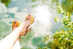 Weibliche Füße über dem Wasser Stockfotos