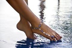 Weibliche Füße über dem Wasser und dem Armband auf Knöchel Stockbilder