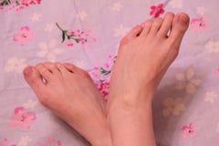 Weibliche Füße auf der Couch Stockbild