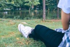 Weibliche Füße auf grünem Gras im Park Lizenzfreie Stockfotos