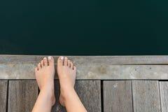 Weibliche Füße auf hölzerner Plattform durch das Meer Frauen-Füße mit den Weiß gemalten Zehennägeln auf hölzernem Hintergrund Stockbild