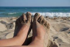 Weibliche Füße auf weißem sandigem Strand Stockbilder