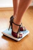 Weibliche Füße in den Farbstiletten mit Gewichtsskala Stockbilder