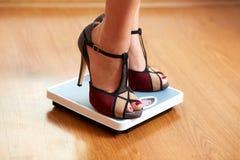 Weibliche Füße in den Farbstiletten mit Gewichtsskala Lizenzfreies Stockfoto