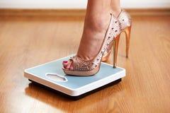 Weibliche Füße in den goldenen Stiletten auf einer Gewichtsskala Lizenzfreie Stockfotos