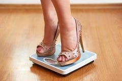 Weibliche Füße in den goldenen Stiletten auf einer Gewichtsskala Stockfotos
