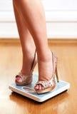 Weibliche Füße in den goldenen Stiletten mit Gewichtsskala Stockfotografie