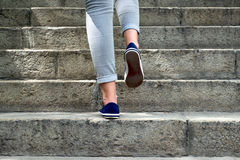 Weibliche Füße in den Turnhallenschuhen, zum der Treppe zu klettern Lizenzfreie Stockbilder