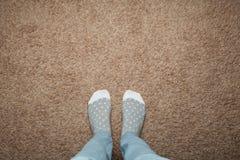 Weibliche Füße in den warmen Socken gegen einen Hintergrund des braunen Teppichs, Raum für Text stockfoto