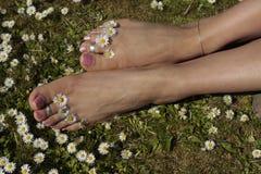 Weibliche Füße, die auf Grasrasen mit Blumen sich entspannen Stockfotografie