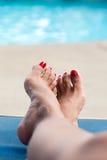 Weibliche Füße, die durch das poo sich entspannen Stockbild