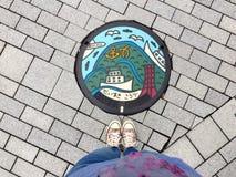 Weibliche Füße die Turnschuhe tragend, die vor typischem verziertem Einsteigeloch von Kobe City, Japan stehen lizenzfreies stockbild