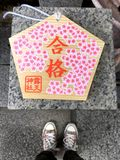 Weibliche Füße, die vor einer votive Plakette Ema in Osaka stehen lizenzfreies stockbild