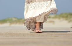 Weibliche Füße, die vorwärts am Strand gehen Lizenzfreies Stockfoto