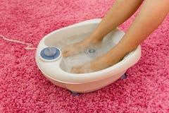 Weibliche Füße in einem vibrierenden Fuß Massagerhaus Stockfotos
