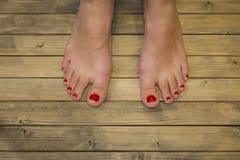 Weibliche Füße herein auf Bretterboden oder Hintergrund lizenzfreie stockfotos