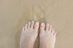 Weibliche Füße im Sand Lizenzfreie Stockfotos