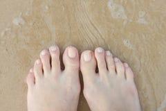 Weibliche Füße im Sand Stockbild