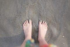 Weibliche Füße im Sand durch das Meer Stockfoto