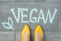 Weibliche Füße mit dem Textstrengen vegetarier geschrieben auf grauen Bürgersteig Lizenzfreie Stockfotos