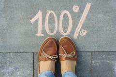 Weibliche Füße mit Text 100 Prozent geschrieben auf grauen Bürgersteig Lizenzfreie Stockbilder