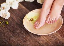 Weibliche Füße mit Wassertropfen, Badekurortschüsseln, Tüchern, Blumen und Kerzen Stockfoto