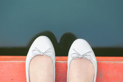 Weibliche Füße am Rand des Piers Lizenzfreies Stockfoto