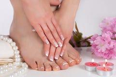 Weibliche Füße und Hände mit französischem Nagellack im Badekurortsalon mit dekorativer rosa Blume, Kerzen, Perlen und Tuch lizenzfreies stockbild