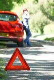 Weibliche Fahrer-Broken Down On-Land-Straße mit Warnzeichen herein F stockbild