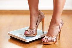 Weibliche Füße in den goldenen Stiletten mit Gewichtsskala Lizenzfreie Stockbilder
