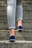 Weibliche Füße in den Turnhallenschuhen, zum der Treppe zu klettern Stockfotos